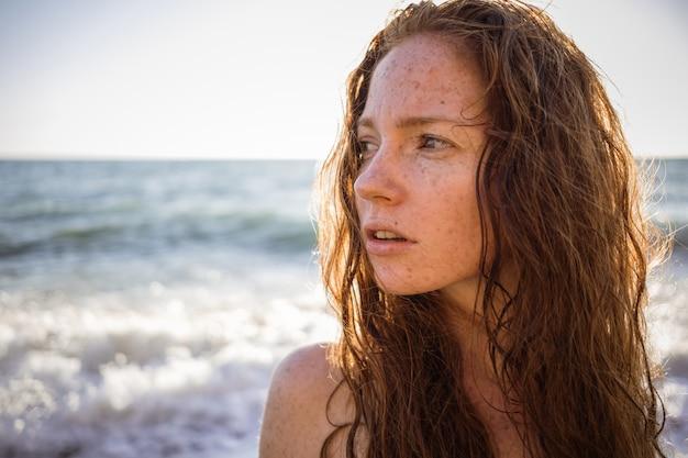 Portret van sproeterig mooie vrouw op zonsondergang strand