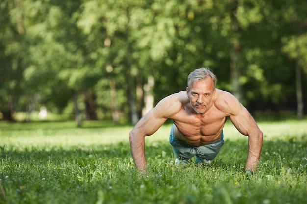 Portret van sterke doelgerichte volwassen man met gespierde armen push-ups doen vanaf de grond in het park