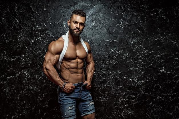 Portret van sterke gezonde knappe atletische man fitness model poseren in de buurt van donkere muur