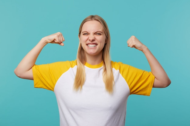 Portret van sterke jonge mooie langharige blonde vrouw die haar handen opheft terwijl ze kracht demonstreert en haar gezicht fronst, geïsoleerd op blauwe achtergrond