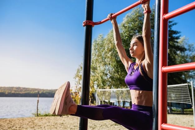 Portret van sterke jonge vrouw in sportkleding die op muur hangen