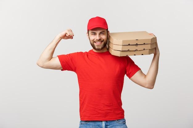 Portret van sterke knappe leveringsmens die zijn spier buigt en pizzadoospakketten houdt