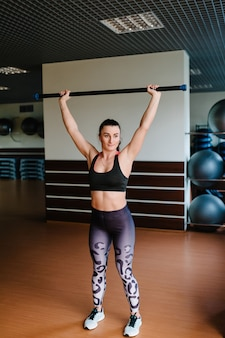 Portret van sterke sportieve vrouw die oefening met lichaamsstaaf in gymnastiek doet