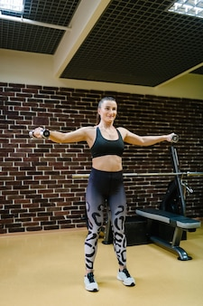 Portret van sterke sportieve vrouw doen oefening met halters in sportschool