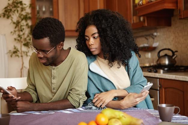 Portret van stiekeme en jaloerse jonge afrikaanse vrouw die haar echtgenoot bespioneert