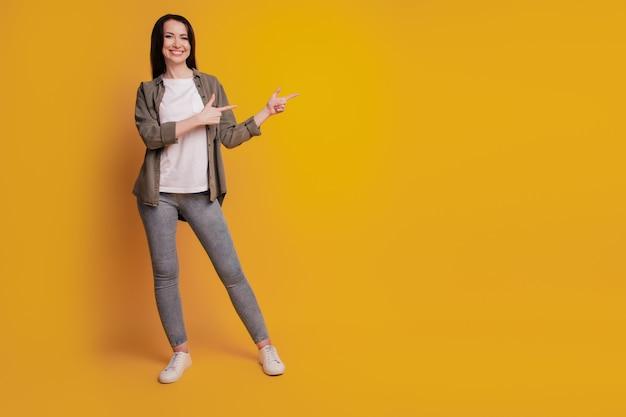 Portret van stijlvol kaukasisch meisje wijst opzij geïsoleerd over gele achtergrond