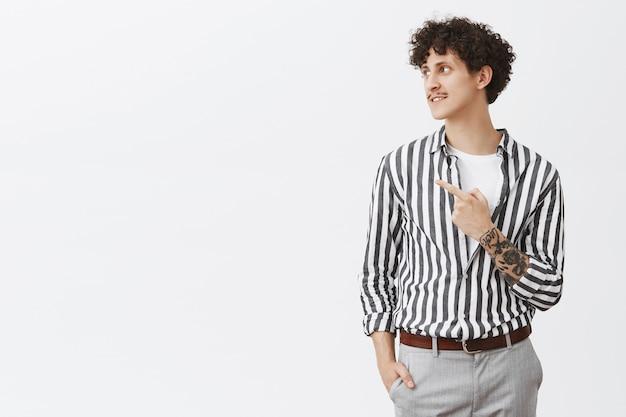 Portret van stijlvol knap en zelfverzekerd modern hipster mannelijk model met snor krullend donker haar en tatoeages wijzen en starend naar links met tevreden charmante glimlach over grijze muur