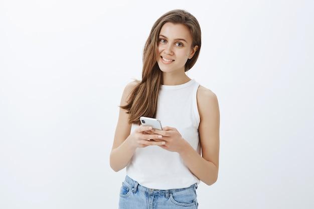 Portret van stijlvol modern jong meisje met behulp van smartphone en gelukkig glimlachen