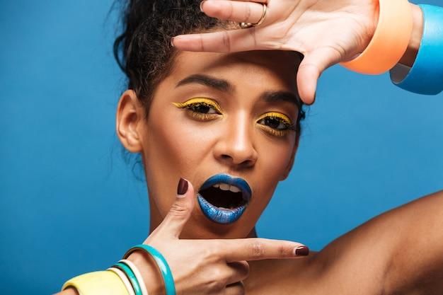 Portret van stijlvolle aanbiddelijke vrouw met kleurrijke make-up en krullend haar in broodje gebaren op camera met glimlach, geïsoleerd over blauwe muur