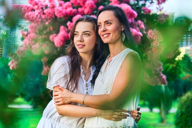 Portret van stijlvolle aantrekkelijke glimlachende blije gelukkige moeder en jonge dochter omhelzen elkaar in een park buiten