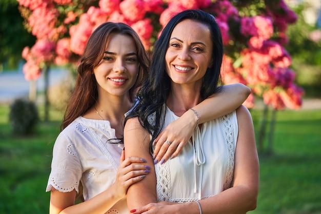 Portret van stijlvolle aantrekkelijke glimlachende vrolijke gelukkige moeder en dochter knuffelen en kijken naar een camera samen in een park buiten