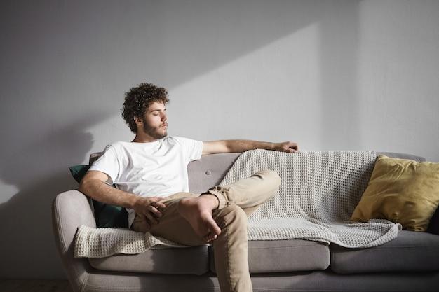 Portret van stijlvolle aantrekkelijke jonge ongeschoren man met wit t-shirt en beige spijkerbroek die blootsvoets op de bank thuis zit, de ogen gesloten houdt, genietend van de zon, zich ontspannen en zorgeloos voelt