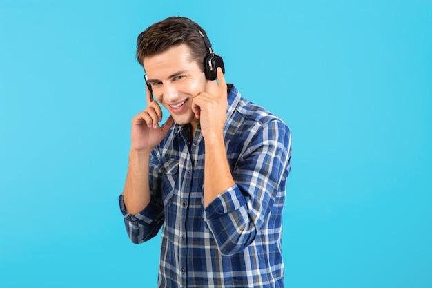 Portret van stijlvolle aantrekkelijke knappe jongeman luisteren naar muziek op draadloze koptelefoon met plezier moderne stijl gelukkig emotionele stemming geïsoleerd op blauwe achtergrond geruit overhemd dragen