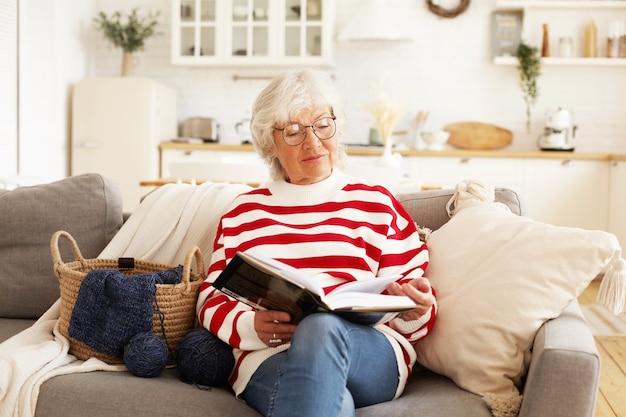 Portret van stijlvolle aantrekkelijke vrouwelijke gepensioneerde m / v in ronde brillen thuis ontspannen met goed boek. blije bejaarde die bril draagt, bestseller leest, comfortabel op bank zit