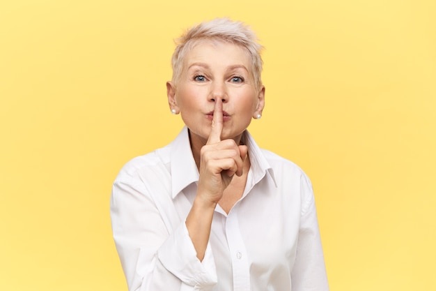 Portret van stijlvolle aantrekkelijke zakenvrouw van middelbare leeftijd in wit overhemd met de vinger op haar lippen en vraagt u te zwijgen over het handelsgeheim, shh gebaar maken.