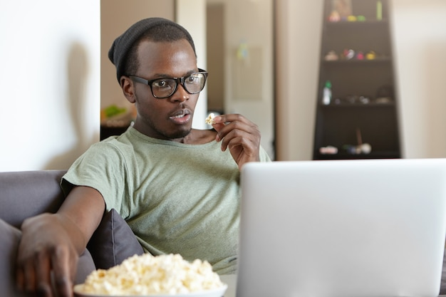 Portret van stijlvolle afro-amerikaanse man met laptop thuis