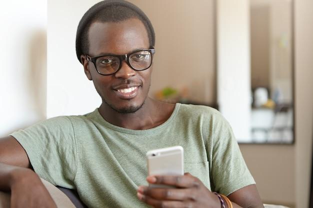 Portret van stijlvolle afro-amerikaanse man met smartphone thuis