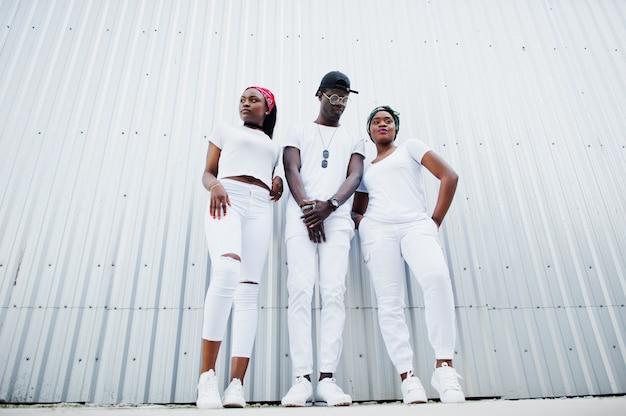 Portret van stijlvolle afro-amerikaanse man met twee meisjes, slijtage op witte kleding, tegen stalen muur. straatmode van jonge zwarte mensen.