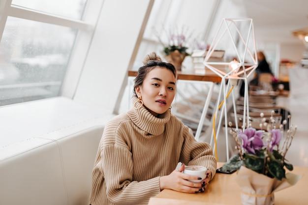 Portret van stijlvolle aziatische vrouw in beige trui met kopje koffie