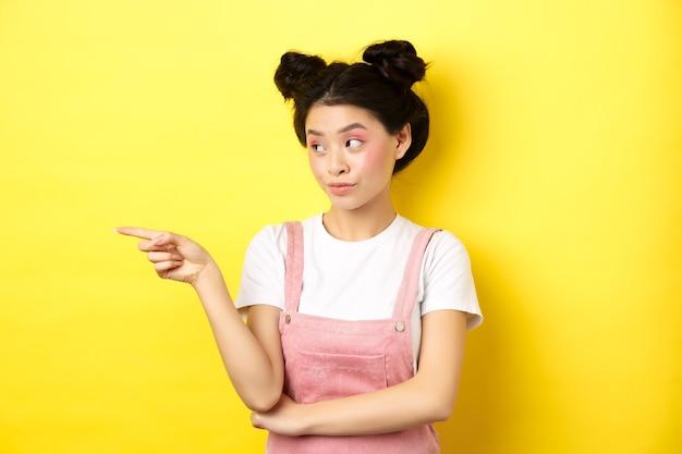 Portret van stijlvolle aziatische vrouw met make-up en zomerkleding, wijzend en links kijkend naar logo, staande geïntrigeerd op geel.