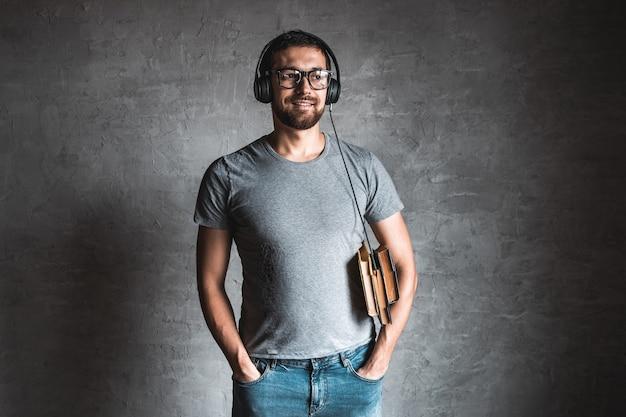 Portret van stijlvolle bebaarde man gekleed in grijs casual t-shirt luisteren audioboek met zijn koptelefoon en op de grijze achtergrond