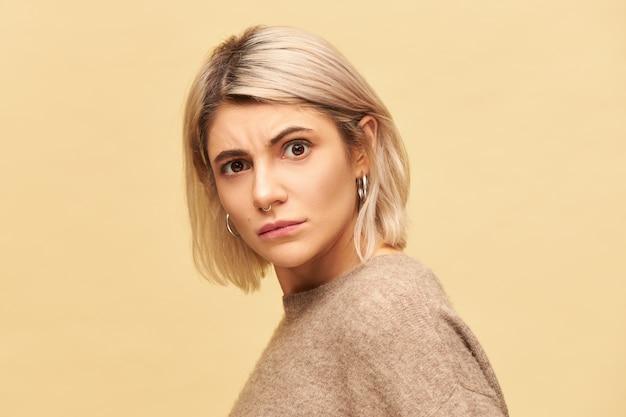 Portret van stijlvolle blonde jonge vrouw, gekleed in gezellige trui staren in verontwaardiging, fronsen wenkbrauwen, walgen van slechte geur, stinken. verontwaardigd meisje uiting van ongenoegen