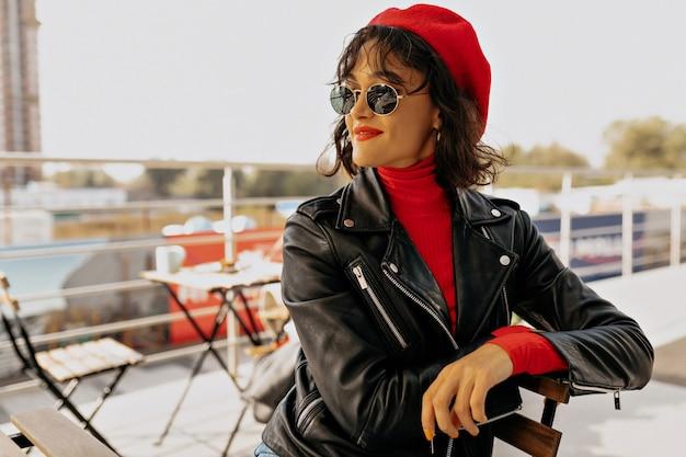 Portret van stijlvolle charmante vrouw in rode baret met rode lippen zittend op terras close-up