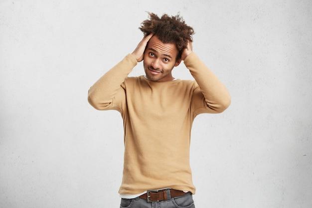 Portret van stijlvolle donkere man met krullend haar, draagt een spijkerbroek en trui, houdt de handen op het hoofd