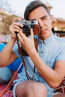 Portret van stijlvolle fotograaf in trendy lichtblauw denimoverhemd dat foto neemt op onscherpe achtergrond