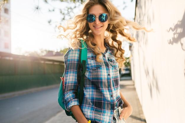 Portret van stijlvolle glimlachende gelukkige blonde vrouw die in straat loopt