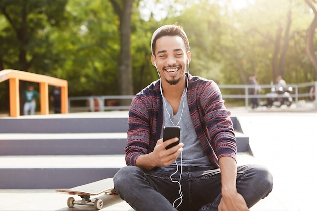 Portret van stijlvolle hipster man voelt zorgeloos zit op trappen buiten, rust na een lange training skateboard rijden,