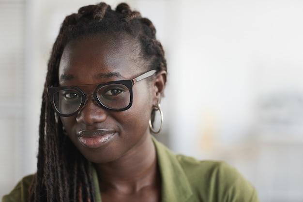 Portret van stijlvolle jonge afrikaanse vrouw bril dragen en glimlachen naar de camera tegen onscherpe witte achtergrond, kopie ruimte close-up