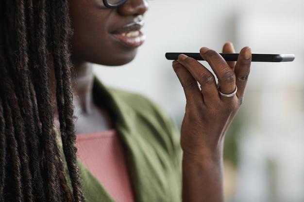 Portret van stijlvolle jonge afrikaanse vrouw spraakbericht opnemen via smartphone in kantoor, kopieer ruimte close-up