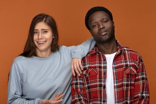 Portret van stijlvolle jonge donkerhuidige man met een ernstige knorrige blik die wordt beledigd met een grap of grap gemaakt door zijn vriendin die naast hem lacht, met geen idee van gezichtsuitdrukking