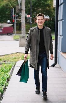 Portret van stijlvolle jonge man lopen met boodschappentassen in de open lucht
