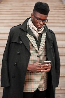 Portret van stijlvolle jonge man texting op zijn telefoon