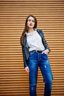 Portret van stijlvolle jonge vrouw die op leerjasje en gescheurde jeans in straten van stad draagt