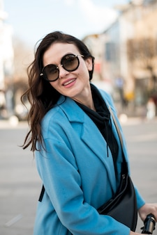 Portret van stijlvolle jonge vrouw met zonnebril