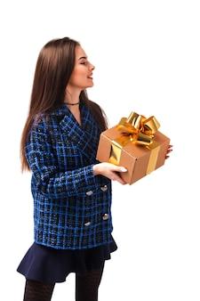 Portret van stijlvolle jonge zakenvrouw in blauwe jas presenteert geschenkdoos op witte geïsoleerde achtergrond. leuke sexy dame in poseren en tonen van emoties. concept van stijl, mode in valentijnsdag