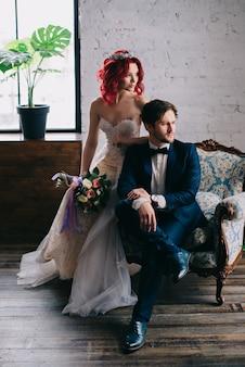 Portret van stijlvolle jonggehuwden zittend in een vintage stoel