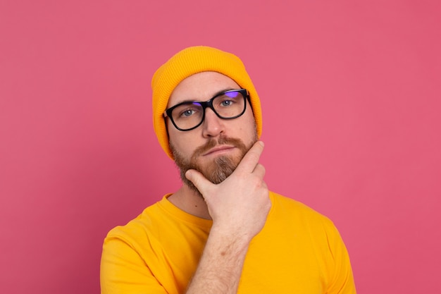 Portret van stijlvolle knappe europese bebaarde man in casual geel overhemd hoed en bril op roze achtergrond