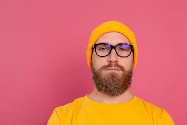 Portret van stijlvolle knappe europese bebaarde man in casual gele overhemdshoed en bril op roze