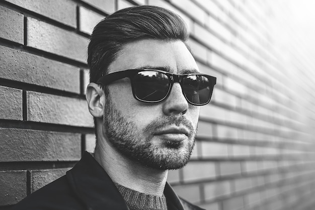 Portret van stijlvolle knappe jonge man met varkenshaar permanent buiten en leunend op bakstenen muur. man met jas, trui en zonnebril.