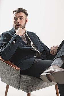 Portret van stijlvolle knappe jonge man zit tegen wit. man met jas