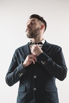 Portret van stijlvolle knappe jongeman permanent in studio tegen wit. man met jas