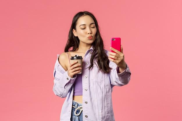 Portret van stijlvolle, knappe vrouwelijke blogger, lifestyle-internetbeïnvloeder die selfie neemt met afhaalkoffie uit haar favoriete café, mobiele telefoon vasthoudt, pruilt voor kus en ogen sluit