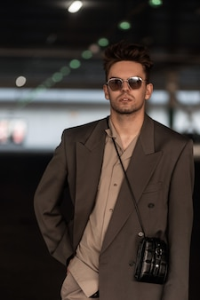 Portret van stijlvolle knappe zakenman met vintage zonnebril in mode grijs pak met handtas in parking