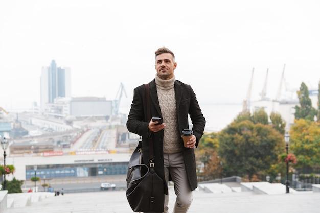 Portret van stijlvolle man 30s dragen jas met behulp van mobiele telefoon en afhaalmaaltijden koffie te houden, tijdens een wandeling door de stad straat