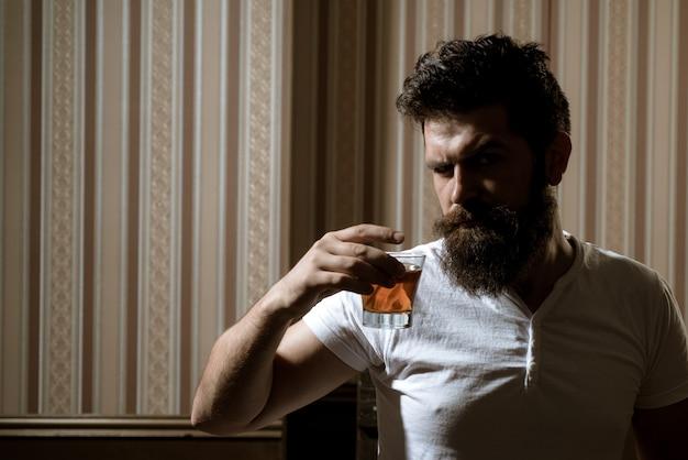 Portret van stijlvolle man baard. knappe stijlvolle bebaarde man drinkt thuis na het werk. dronken man. stijlvolle man.