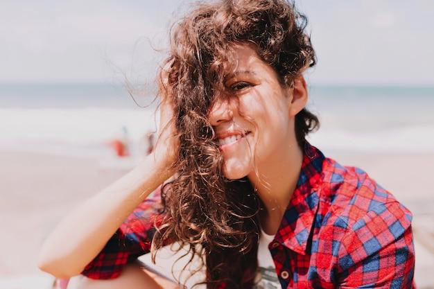 Portret van stijlvolle mooie jonge dame met donker golvend haar en mooie ogen, zittend door de oceaan in zonlicht. zomer, recreatie, vakantie, blije emoties
